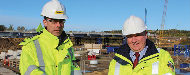 Farrans' Stephen McCaffrey (left) on site in Sunderland with Moore Concrete's Richard Whiteside as the new bridge over the River Wear continues to take shape behind them.