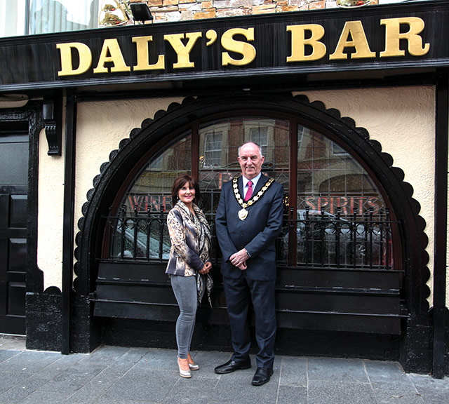 Maura Daly, owner of Daly's Bar, one of the 102 Mid Ulster premises which benefitted from investment provided by the Council's Shop Improvement Scheme, with the Council Chairman, Councillor Trevor Wilson.